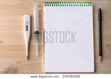 the syringe thermometer and pen lying on the table with a notebook, wooden table