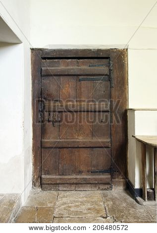 An old traditionally built wooden door with wooden latches and iron hingles in a vertical format