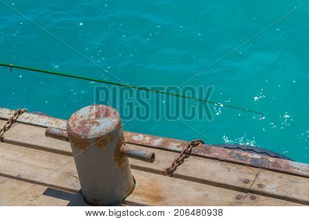 Old rusty bollard with metal chain on pier with water.