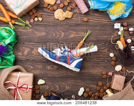 Dutch holiday Sinterklaas background with gifts, pepernoten, sweets and childrens shoe with carrots on old wooden table. Flat lay with copy space. Top view.