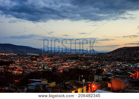Puebla, Mexico. Aerial view of Puebla, Mexico at sunset. Mountains at the background, dark city with illuminated buildings at night