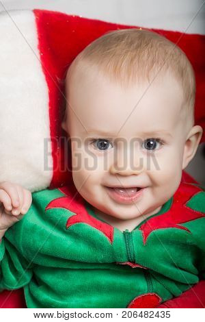 Winter holiday and vacation. Xmas party celebration. New year baby on hand of mother. Christmas child with happy face. Elf kid in costume of santa.