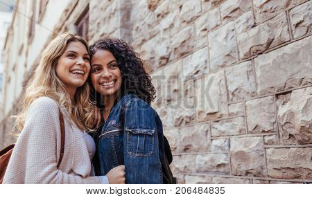 Young women standing together beside a stone wall. Two smiling women posing for a photograph outdoors.