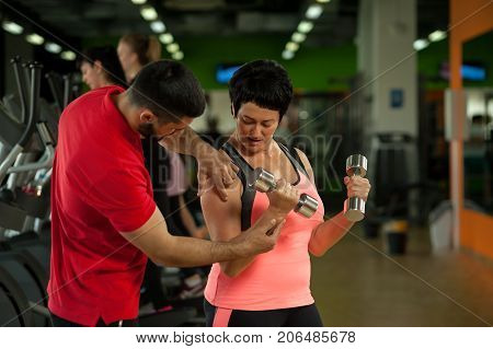 Male fitness coach assisting middle aged female client in gym. Brunette woman exercising with dumbbells in modern fitness center. Healthy lifestyle concept.