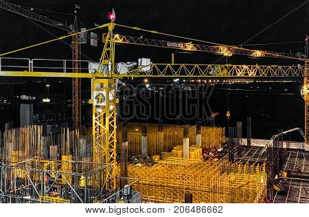 BANGKOK THAILAND - SEPTEMBER 03: Crane continues to operate through the evening on a construction site of a building on September 03 2017 in Bangkok.