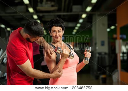 Young personal coach working with middle aged woman in gym. Female brunette exercising with dumbbells. Healthy lifestyle, fitness and sports concept.