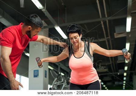 Middle aged brunette woman working out with personal coach in gym. Attractive woman doing shoulders exercises with dumbbells. Healthy lifestyle, fitness and sports concept.