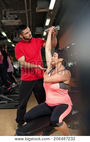 Young male fitness coach with middle aged female client in gym. Attractive brunette woman working out with personal trainer. Healthy lifestyle, fitness and sports concept.