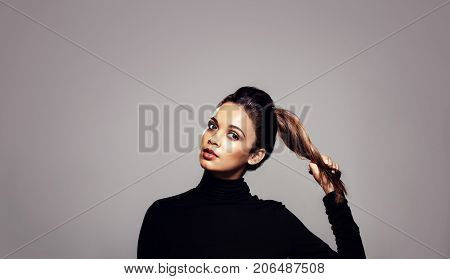 Strong healthy hair. Beautiful young woman holding her ponytail over grey background.