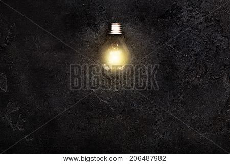 One Glowing light bulb in the middle of dark shimmering background. Creativity and new idea concept copy space