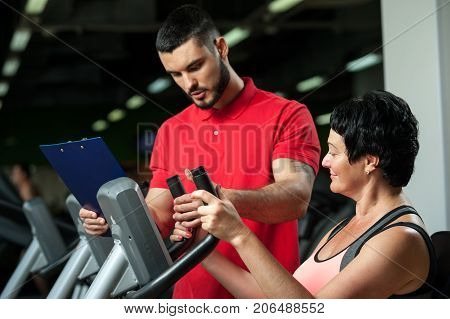 Middle aged woman working with personal coach in gym. Brunette female exercising on machine with assistance of fitness coach. Healthy lifestyle, fitness and sports concept.