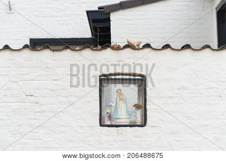 small box with virgin mary in a white brick wall