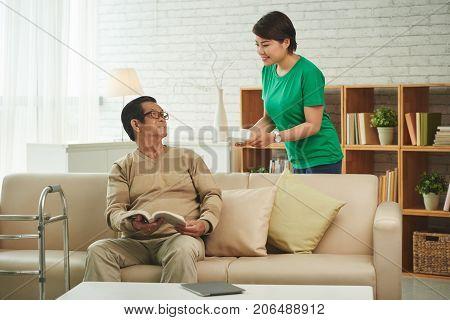 Nurse bringing cup of tea to senior Vietnamese man