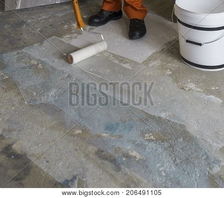 Renovation of house. Worker puts primer with roller on concrete floor