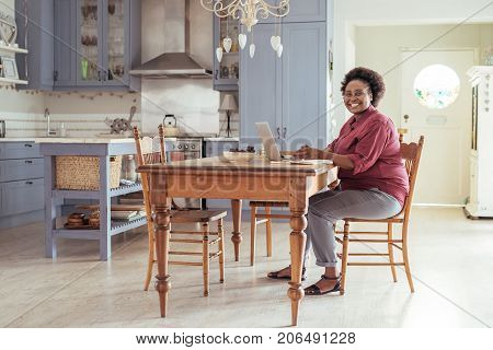 Portrait of a smiling young African woman sitting alone at her kitchen table at home working online with a laptop