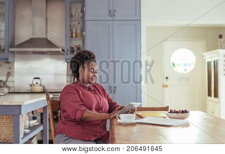 Young African woman sitting alone at her kitchen table at home working on a digital tablet and drinking a cup of coffee