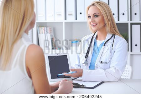 Doctor and patient discussing something while physician pointing into touch pad computer. Medicine and health care concept.