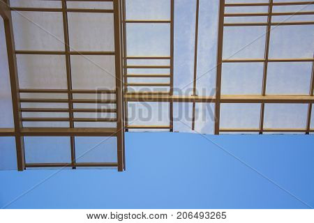 Glass roof of building with background of clear blue sky. Structure of steel roof frame for building construction on sky background.