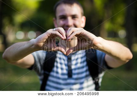 Young man makes hands in shape of love heart. Love concept