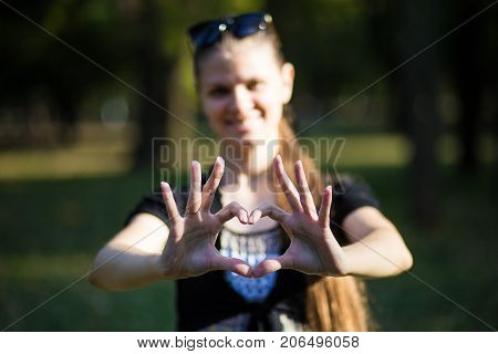 Young woman makes hands in shape of love heart. Love concept