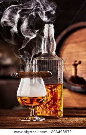 Glass of cognac or brandy with smoking cigar on wooden table.Glass ful of smoke