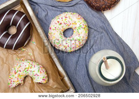 Bottle of milk and colorful donuts with chocolate and icing selective focus
