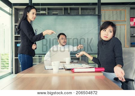 Group of Asian business people looking at businesswoman and blaming colleague for failure bad work results in business meeting room.