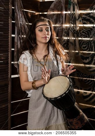Young hippie boho woman having fun ans plays the Jamaica drum. Hippie style on a wooden background