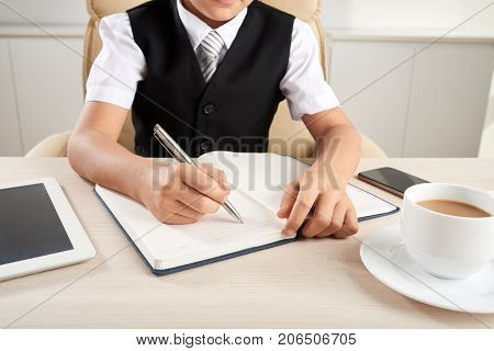 Cropped image of pupil writing essay into textbook