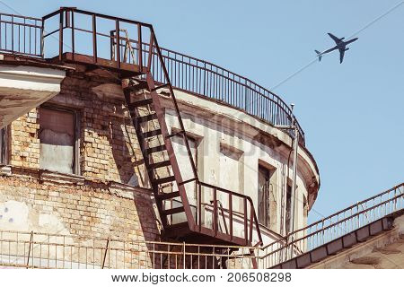 Airplane flying over roof of old weathered house, bottom view low angle view