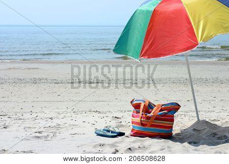 Beach bag, flipflops and umbrella against blue sea and sand