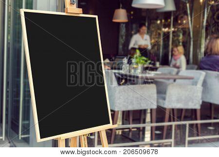 Blank restaurant menu blackboard with blury people inside