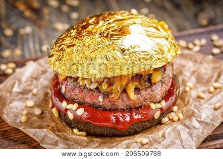 Gold beef burger with a black bun, with arugula and cheese and ketchup sprinkled with pine nuts served on pieces of brown paper on a rustic wooden table, on a dark background. Delicious gold burger. fast food restaurant.