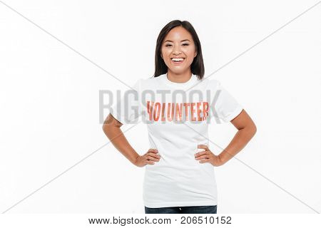 Portrait of a cheerful young asian woman in volunteer t-shirt standing with hands on hips and looking at camera isolated over white background