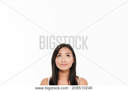 Close up portrait of a pretty young asian woman looking up at a big copy space above her head isolated over white background