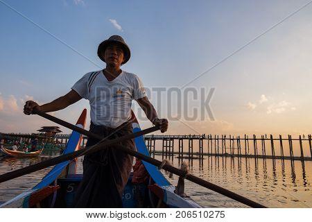 Amarapura Mandalay - December 24 2016: The Burmese are rowing taking tourists to sunset at U Bein Bridge Mandalay Myanmar.