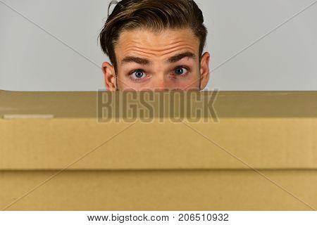 Man Hiding Behind Cardboard Box On Grey Background