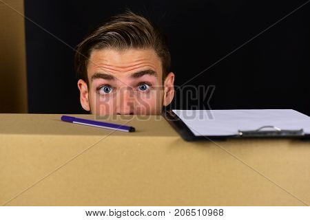 Delivery And Moving In Concept: Man Hiding Behind Cardboard Boxes