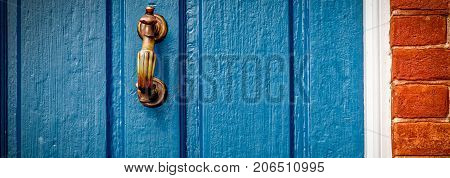 A very rustic looking door knocker mounted on a weathered Virginia door.