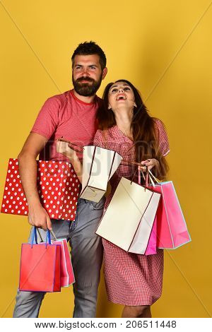 Couple in love holds shopping bags on yellow background. Shopping and spending concept. Man with beard holds red polka dotted box. Guy with beard and girl with happy faces do shopping.