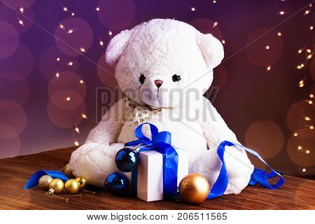 white teddy bear. Close-up of a teddy bear and gift. white teddy bear with gift box with blue ribbonchristmas gold and blue balls