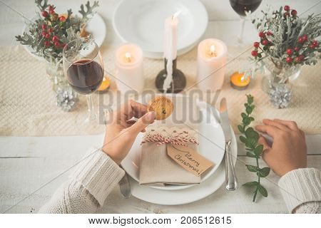 Hands of woman eating cookie after Christmas dinner