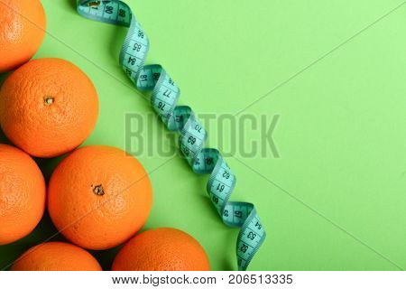 Athletics And Weight Loss Concept. Oranges Near Twisted Measuring Tape