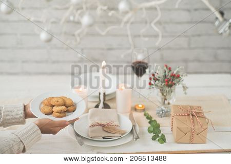 Hands of woman bringing cookies to festive dinner