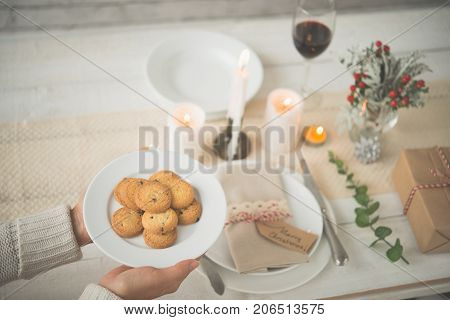 Woman bringing cookies to table with Christmas decoration