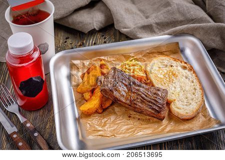Fast food in a restaurant. A well-fried steak with golden crispy french fries and toasted crispy toast. Menu.