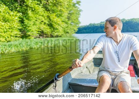 Young Man Rowing Boat On Lake In Virginia During Summer In White Shirt Looking Back Splashing Water
