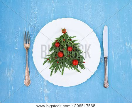 Christmas fir tree made of arugula and cherry tomatos on white plate with silverware on blue rustic background.
