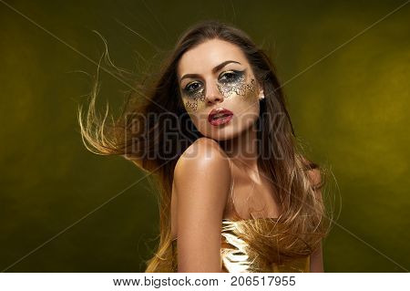 Photo of a pretty young girl with a long dark hair. Her skin is smooth and healthy. She wears fantastic make-up in golden tones and red lipstick made by an artist.
