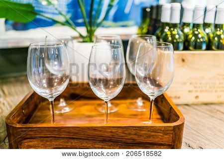 Closeup Of Empty Wine Glasses On Tray With Wooden Crate Of Bottles On Table In Room